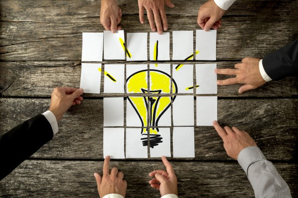 High angle view of businessmen hands touching white papers arranged on a rustic wooden table forming a yellow light bulb. Conceptual for bright business ideas and innovations.