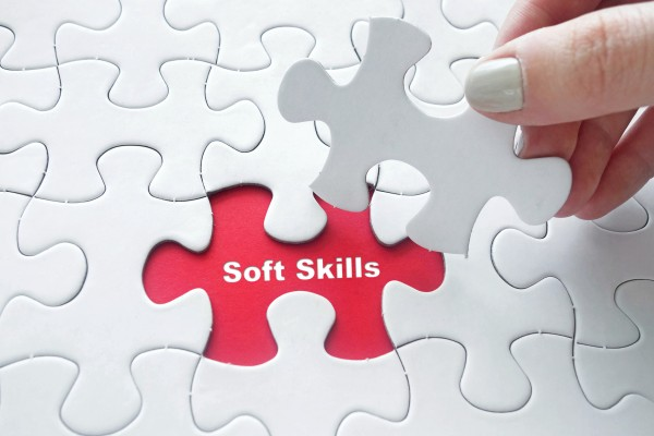 Close up of girl's hand placing the last jigsaw puzzle piece with word Soft Skills