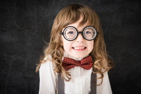 Curly-headed mischief nerd kid in class. Funny geek against blackboard. Education concept