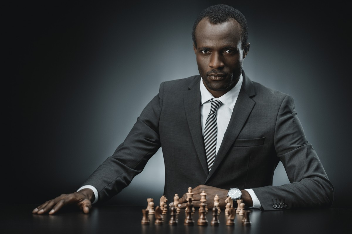 portrait of confident african american businessman with chess figures on table looking at camera isolated on black