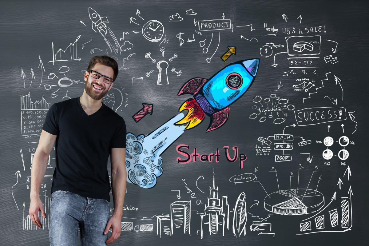 Portrait of cheerful handsome man on chalkboard background with space ship sketch. Entrepreneurship concept